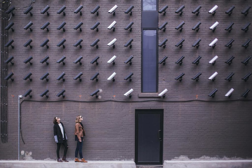 man and woman standing in front of a wall full of cameras