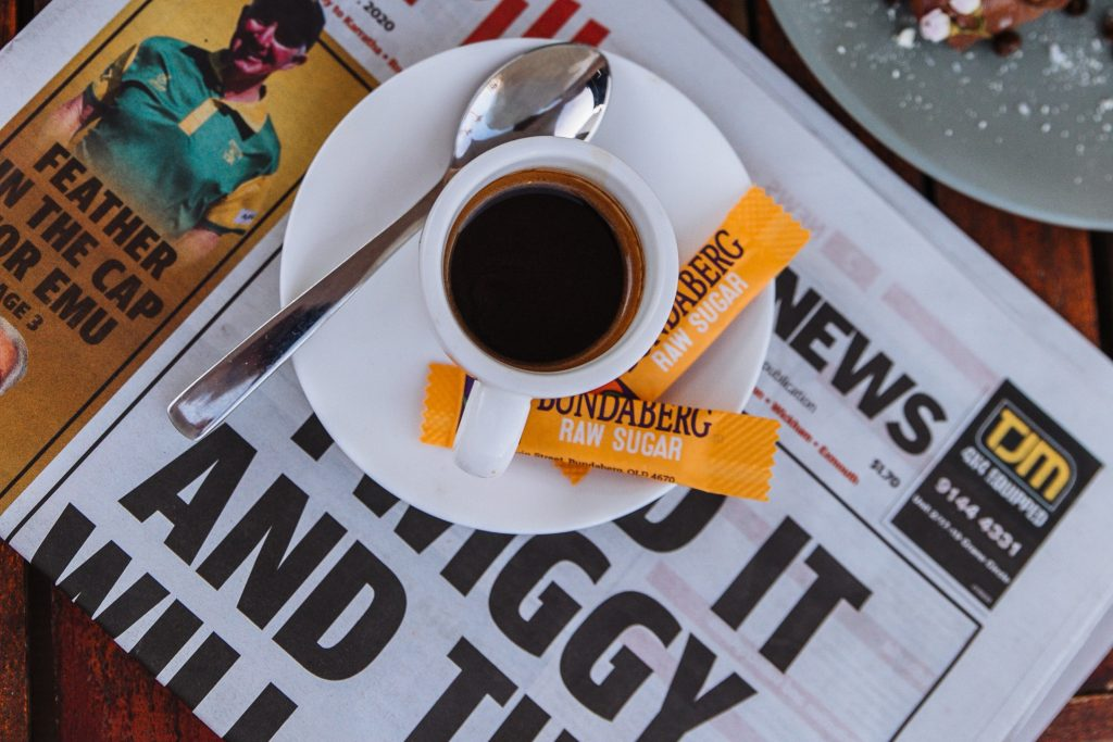 coffee cup and saucer on top of a newspaper