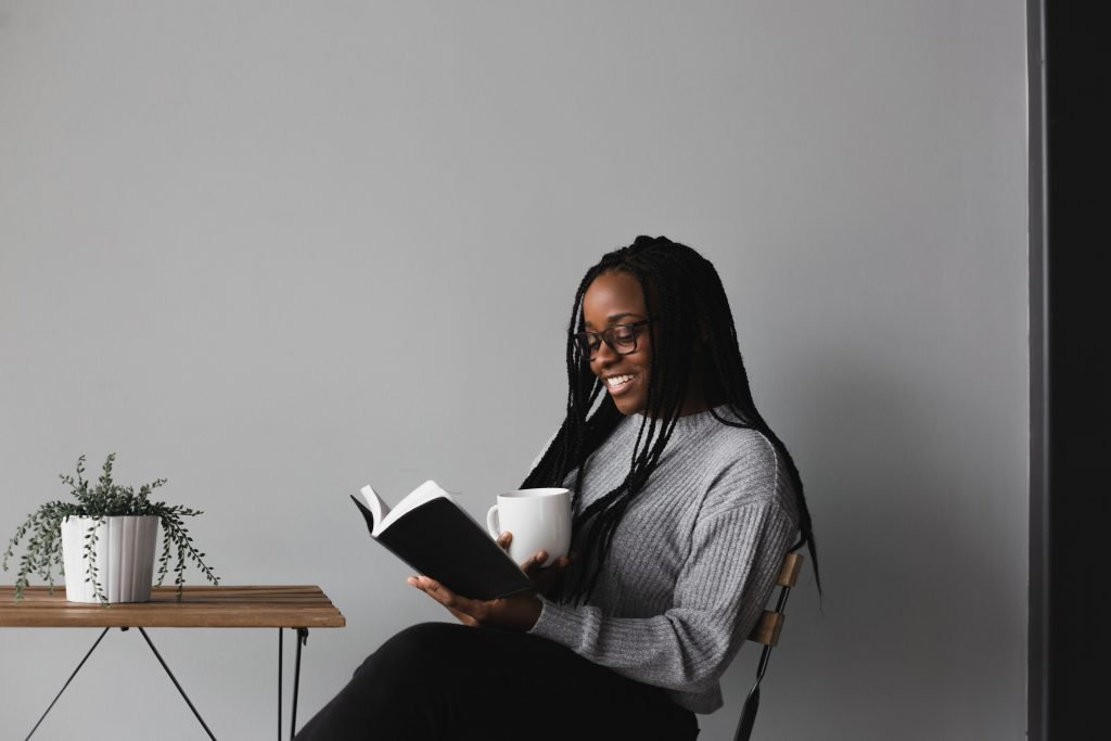smiling girl sitting down reading with a mug in her hand.