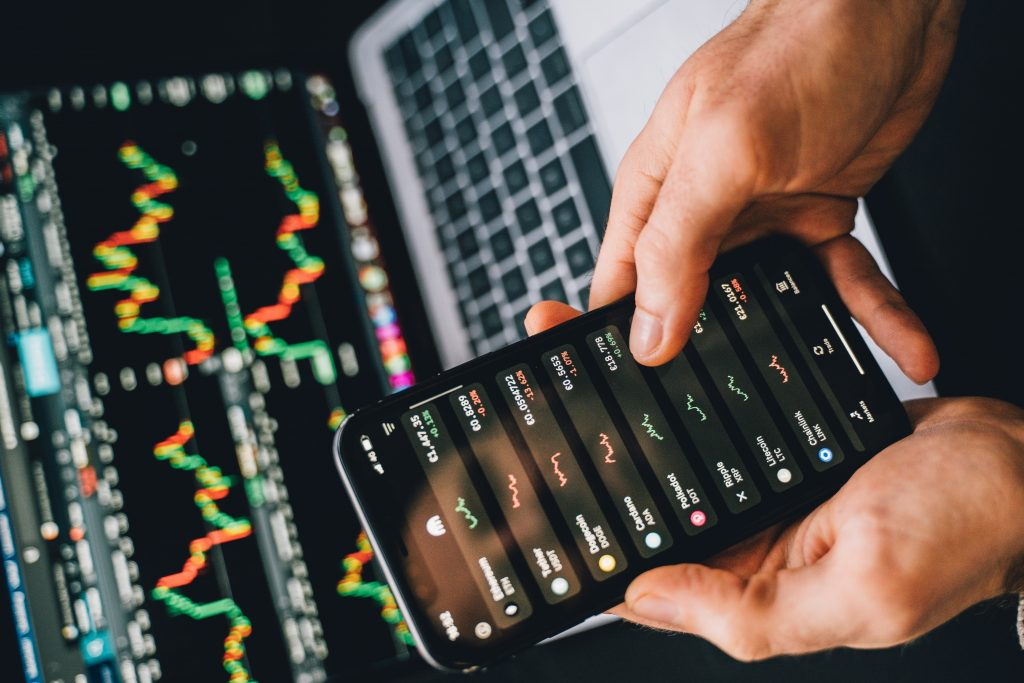 Using computer and phone to trade cryptocurrency. There is a graph on the computer. Hand holding the phone.